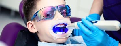 Un garçon avec des lunettes dans la chaise dentaire La bouche a dirigé la lampe de lightpolymerization avec la lumière bleue pour photo libre de droits