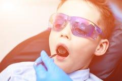 Un garçon avec des lunettes dans la chaise dentaire Le docteur examine la cavité buccale avec un miroir dentaire spécial images libres de droits