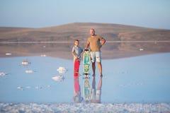 Un garçon avec le père marche le long du rivage du lac sur le panneau de patin Un rivage de lac salt Salt Lake Photographie stock