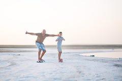 Un garçon avec le père marche le long du rivage du lac sur le panneau de patin Un rivage de lac salt Salt Lake Photographie stock libre de droits