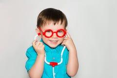 Un garçon avec le petit docteur en verre Images stock