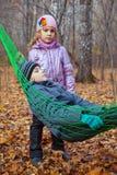 Un garçon avec sa soeur détendant dans un hamac Photos libres de droits