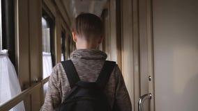 Un garçon avec un sac à dos est sur la voiture de train Le concept du voyage et du tourisme Vacances des vacances Course du monde banque de vidéos