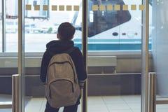 Un garçon avec un sac à dos se tient près de la porte en verre à l'autobus de attente de transfert d'aéroport à l'avion images libres de droits