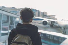 Un garçon avec un sac à dos se tient près de la porte en verre à l'autobus de attente de transfert d'aéroport à l'avion image stock