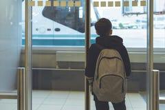 Un garçon avec un sac à dos se tient près de la porte en verre à l'autobus de attente de transfert d'aéroport à l'avion Déviation image libre de droits