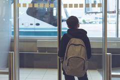 Un garçon avec un sac à dos se tient près de la porte en verre à l'autobus de attente de transfert d'aéroport à l'avion Déviation photographie stock libre de droits