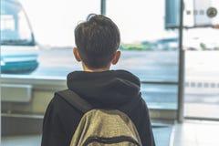 Un garçon avec un sac à dos se tient près de la porte en verre à l'autobus de attente de transfert d'aéroport à l'avion Déviation photo stock