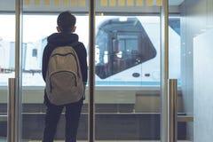 Un garçon avec un sac à dos se tient près de la porte en verre à l'autobus de attente de transfert d'aéroport à l'avion Déviation photo libre de droits