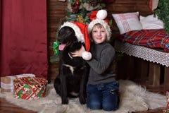 Un garçon avec un chien noir dans des chapeaux de Noël Photographie stock
