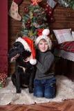 Un garçon avec un chien noir dans des chapeaux de Noël Photos libres de droits