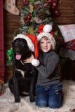 Un garçon avec un chien noir dans des chapeaux de Noël Photos stock