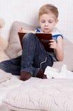 Un garçon avec un livre Images stock