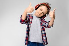 Un garçon beau dans une chemise de plaid, la chemise grise et des jeans se tient sur un fond gris Un garçon dans des écouteurs ro Image stock