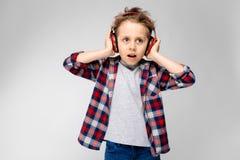 Un garçon beau dans une chemise de plaid, la chemise grise et des jeans se tient sur un fond gris Un garçon dans des écouteurs ro Photos stock