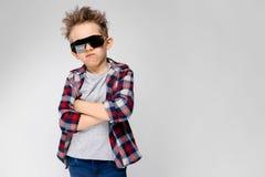 Un garçon beau dans une chemise de plaid, la chemise grise et des jeans se tient sur un fond gris Le garçon dans les lunettes de  Images stock