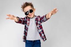 Un garçon beau dans une chemise de plaid, la chemise grise et des jeans se tient sur un fond gris Le garçon dans des lunettes de  Photographie stock