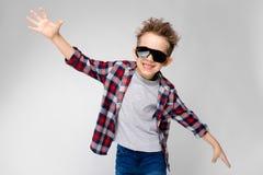 Un garçon beau dans une chemise de plaid, la chemise grise et des jeans se tient sur un fond gris Le garçon dans des lunettes de  Images stock