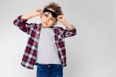 Un garçon beau dans une chemise de plaid, la chemise grise et des jeans se tient sur un fond gris Le garçon dans des lunettes de  Images libres de droits