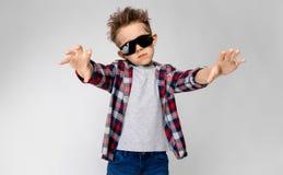 Un garçon beau dans une chemise de plaid, la chemise grise et des jeans se tient sur un fond gris Le garçon dans des lunettes de  Image libre de droits