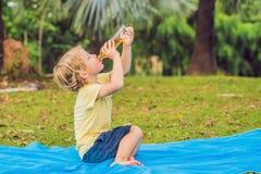 Un garçon boit de la limonade, thé, le kombucha, une orangeade en parc photos libres de droits