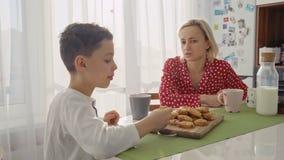 Un garçon caucasien mignon adorable mange le biscuit près de sa jeune mère avec les cheveux blonds banque de vidéos