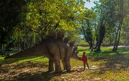 Un garçon choyant un dinosaure en parc Photographie stock