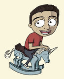 Un garçon conduisant son cheval d'oscillation Images stock