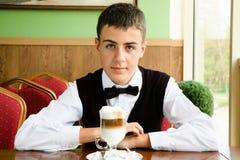 Un garçon d'adolescent appréciant le café dans un café Photographie stock