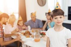 Un garçon dans un chapeau de fête pose dans la perspective d'une table de fête, pour laquelle sa famille Image libre de droits