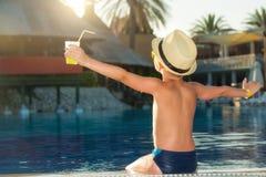Un garçon dans un chapeau de paille avec un cocktail à disposition se reposant sur la piscine photo stock