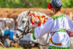 Un garçon dans des vêtements nationaux russes et un poney au festival du sport équestre photo libre de droits