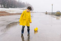 Un garçon dans un imperméable jaune joue un bateau de grand papier dans un magma photo stock
