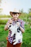 Un garçon dans l'usage de cowboy tenant le lapin la nuque dans la ferme Images stock