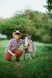 Un garçon dans la chèvre de alimentation d'usage de cowboy avec la carotte dans la ferme Photo libre de droits