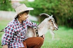 Un garçon dans la chèvre de alimentation d'usage de cowboy avec la carotte dans la ferme Photographie stock