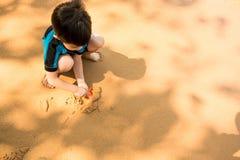 Un garçon dans le costume de natation s'assied sur la plage et joue le sable Photographie stock