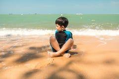 Un garçon dans le costume de natation s'assied sur la plage et joue le sable Image stock