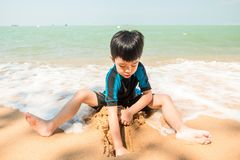 Un garçon dans le costume de natation s'assied sur la plage et joue le sable Image libre de droits