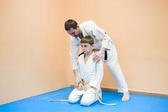Un garçon dans le kimono commencer à s'exercer sur l'aikido image libre de droits