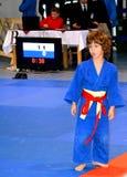 Un garçon dans un concours national de judo Drapeau national de la Roumanie, bleu, jaune, rouge Image libre de droits