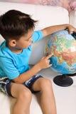 Un garçon de 5-6 ans avec un globe Images libres de droits