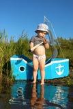 Un garçon de deux ans se tenant avec un bateau fait main et des regards au télescope Images libres de droits