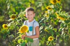 Un garçon de sourire avec un panier des tournesols Garçon de sourire avec le tournesol Un garçon de sourire mignon dans un domain images stock