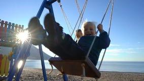 Un garçon de trois ans et une fille de six ans balançant sur une oscillation un matin ensoleillé sur la côte banque de vidéos