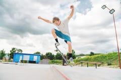 Un garçon en parc de patin faisant un tour sur une planche à roulettes Photographie stock libre de droits
