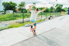 Un garçon en parc de patin faisant un tour sur une planche à roulettes Image stock