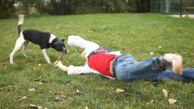 Un garçon et un chien noir et blanc jouent sur l'herbe verte Vacances actives de famille avec des animaux banque de vidéos