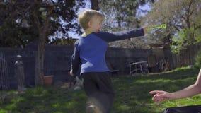 Un garçon et sa maman jouent avec des bulles dans l'arrière-cour clips vidéos