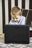 Un garçon et un ordinateur portable photos stock